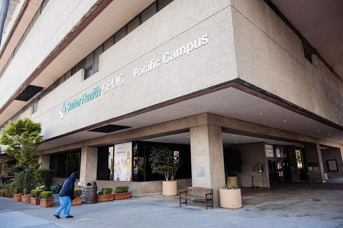 A person is seen walking outside Sutter Health's California Pacific Medical Center in San Francisco, Calif. Sutter Health laid off 400 workers across its hospital network in June 2021.
