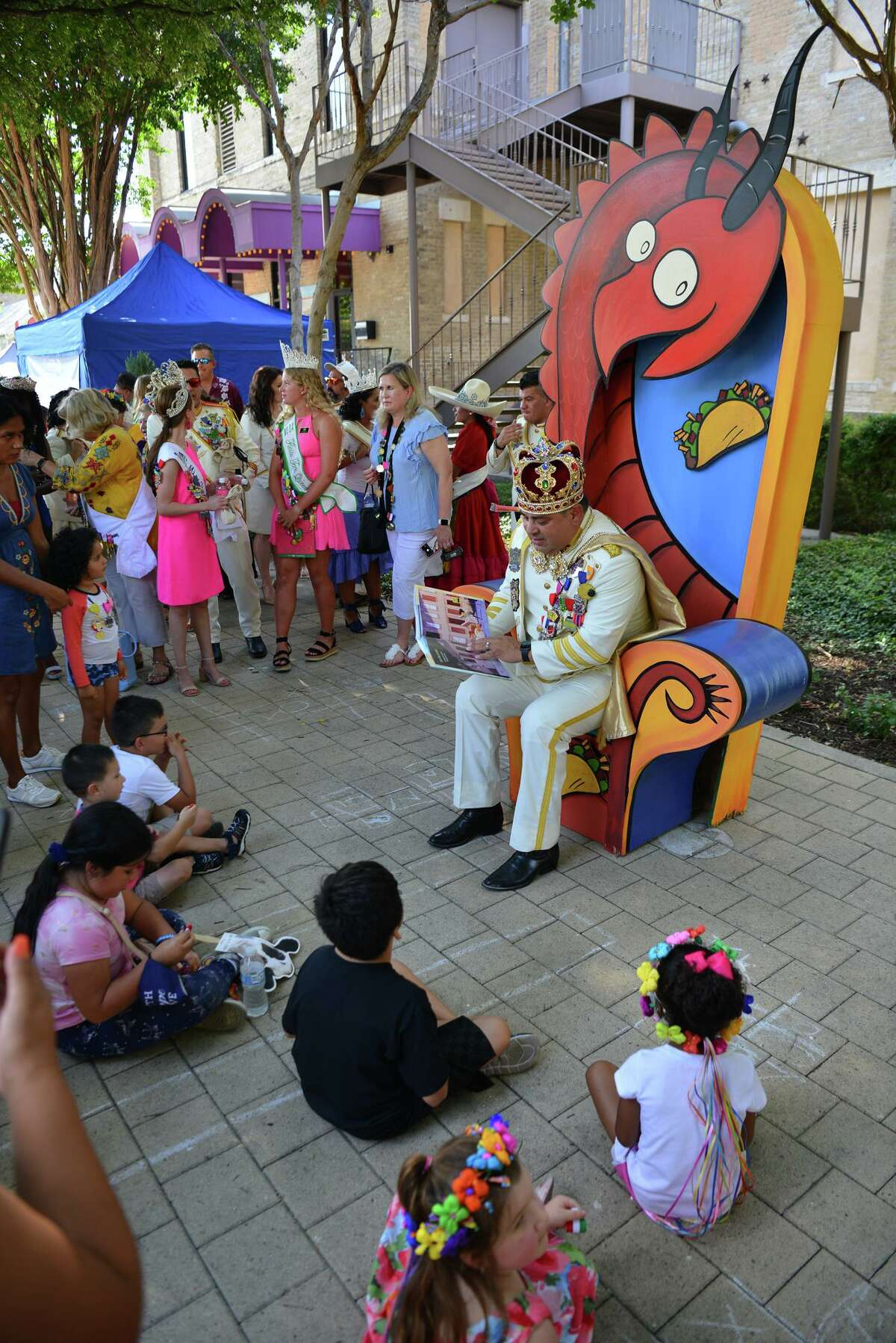 Rey Feo LXXII, Thomas Aguillon, reads to children outside of the Magic Theater on Thursday during Fiesta Fiesta, the start of Fiesta for 2021.