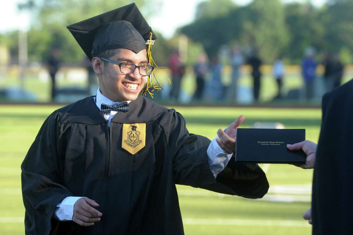 Luis Contreras receives his diploma during graduation for the Trumbull High School Class of 2021, in Trumbull, Conn. June 17, 2021.