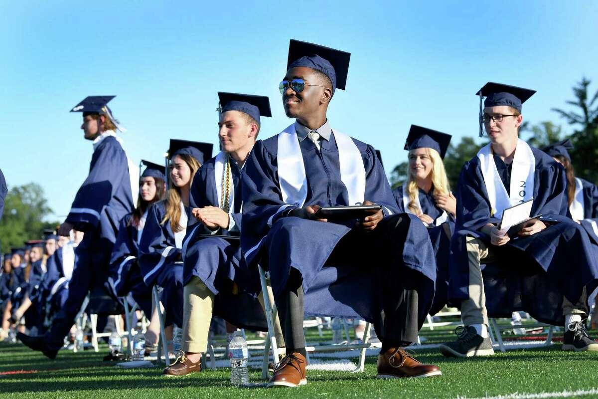 Vaillant Domingue III, center, watches his fellow graduates receive their diplomas at Staples High School graduation ceremonies, Thursday, June 17, 2021 in Westport.