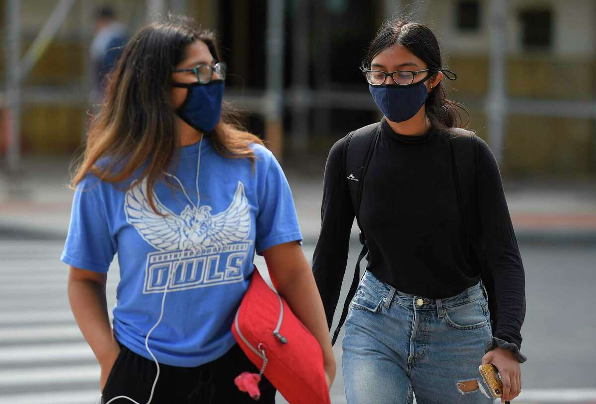 Young people wear masks as they walk through the downtown business district on Sept. 16, 2020 in Stamford.