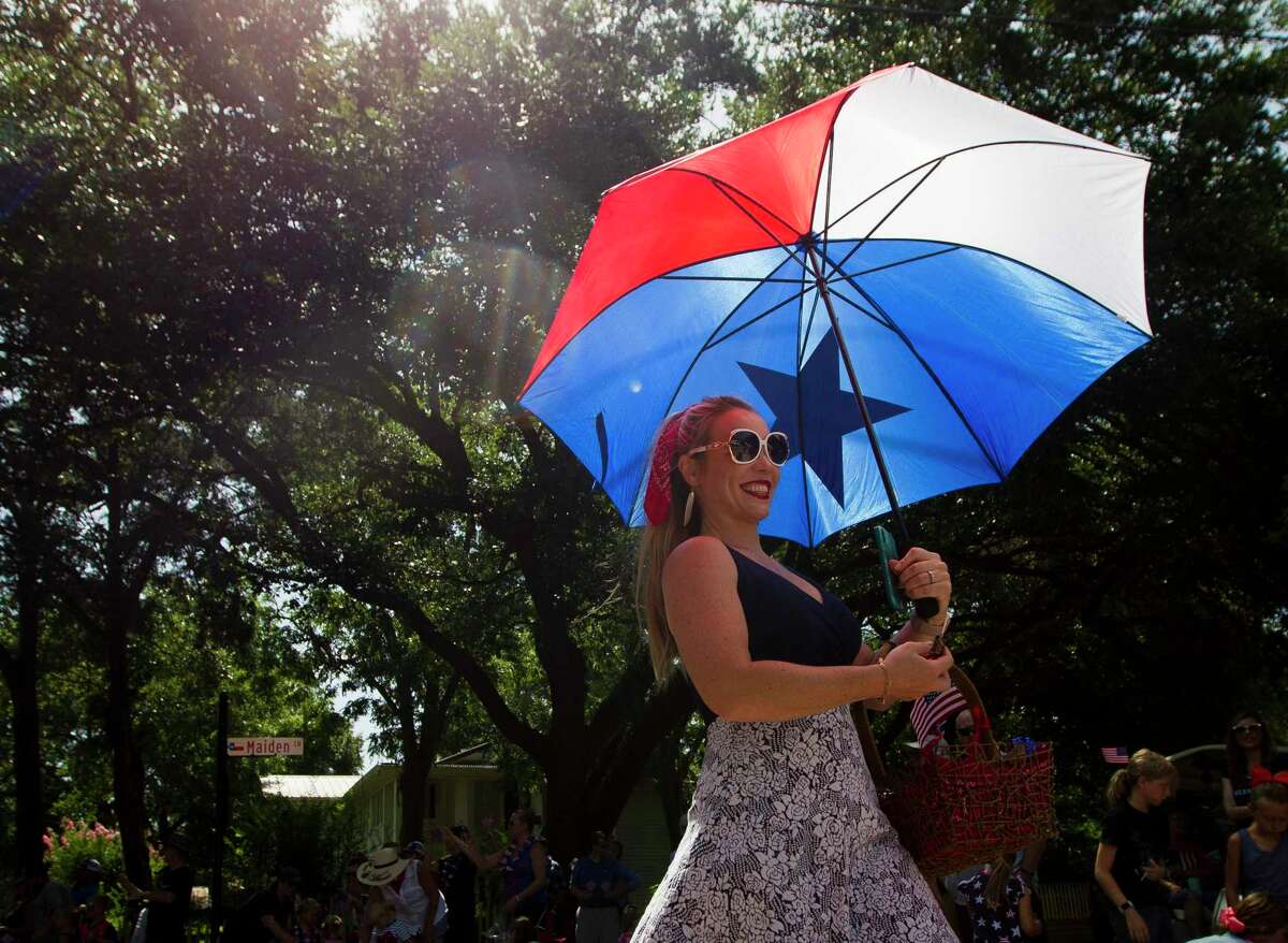Emily Petty walks with a Texas flag themed umbrella as she takes part in theMontgomery's annual Freedom Fest, Saturday, July 6, 2019.