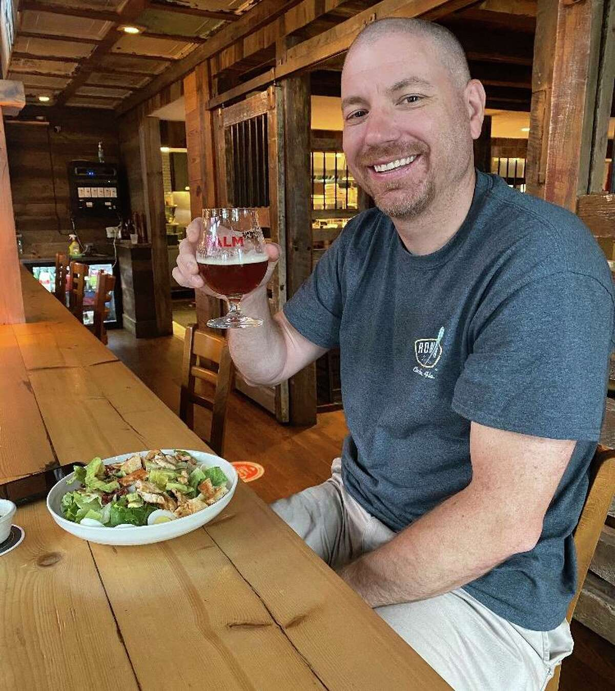 Todd Carpenter raises a glass while enjoying a meal at Red Rooster Pub in Ridgefield.