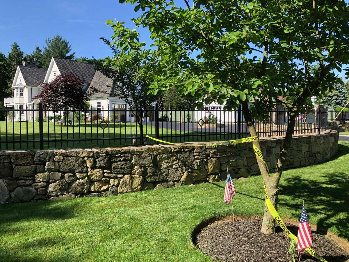 Leftover crime scene tape on Friday at the Westport, Conn., home where a woman and a 7-year-old were found dead on Thursday, June 17, 2021.
