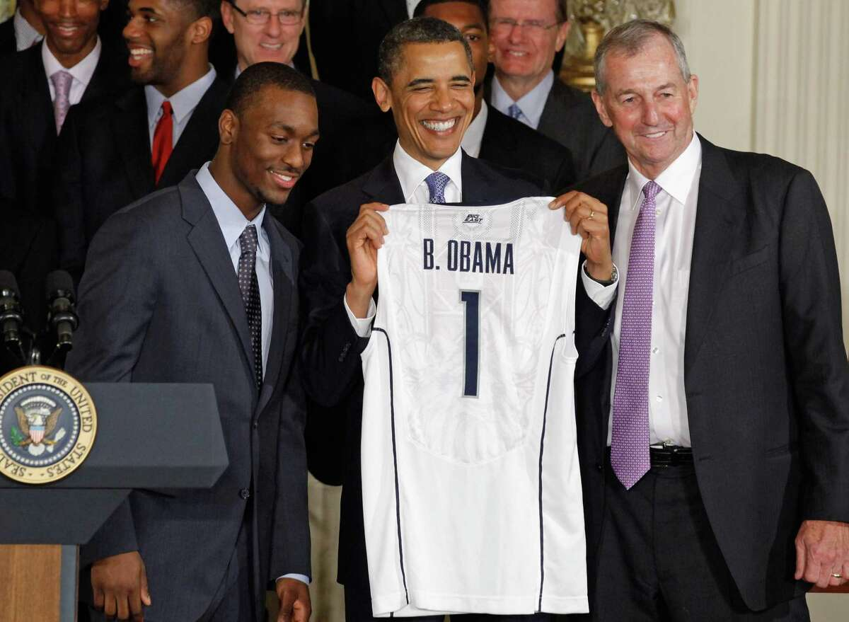 WASHINGTON, DC - MAY 16: U.S. President Barack Obama (C) holds up a jersey while posing for photographs with 2011 NCAA Champion University of Connecticut men's basketball coach Jim Calhoun (R) and team guard Kemba Walker at the White House May 16, 2011 in Washington, DC. UConn earned the national championship with an 11-game run through the postseason, ending with a 53-41 win over Butler in the NCAA title game. (Photo by Chip Somodevilla/Getty Images)