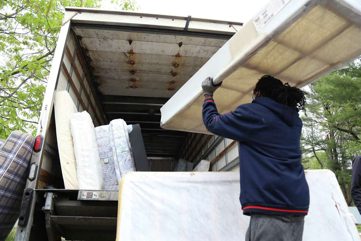 A Park City Green employee loads mattresses in May 2021 at a recycling event in Westport, Conn., hosted by Sustainable Westport and Earthplace. After mandating the recycling of mattresses and paint in recent years, Connecticut could follow the lead of California and New Jersey by mandating plastic bottles have a minimum amount of recycled content.