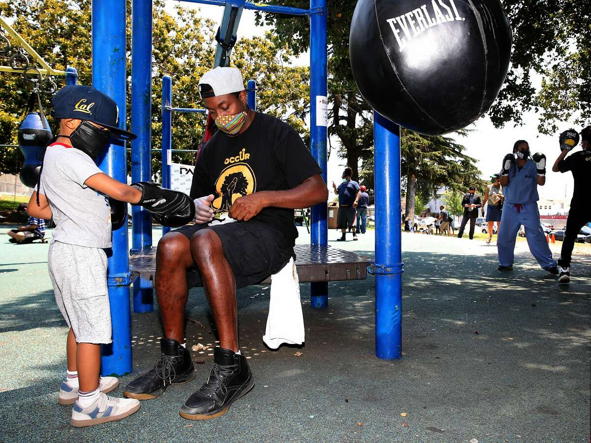 Shomari Carter places a pair of disposable gloves on his son, Onyx Carter, 3, last year in Oakland. A 2013 study found that 70% of Black fathers are involved in their young children's care.