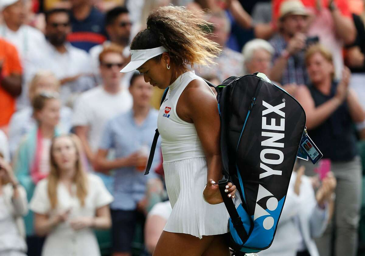 (FILES) In this file photo taken on July 1, 2019, Japan's Naomi Osaka looks downwards as she leaves the pitch after being defeated by Kazakhstan's Yulia Putintseva during their women's singles first round match on the first day of the 2019 Wimbledon Championships at The All England Lawn Tennis Club in Wimbledon, southwest London. - Japanese star Naomi Osaka has withdrawn from Wimbledon, her agent confirmed on June 17, 2021, weeks after the world number two pulled out of the French Open citing her struggle with depression and anxiety. (Photo by Adrian DENNIS / AFP) / RESTRICTED TO EDITORIAL USE (Photo by ADRIAN DENNIS/AFP via Getty Images)