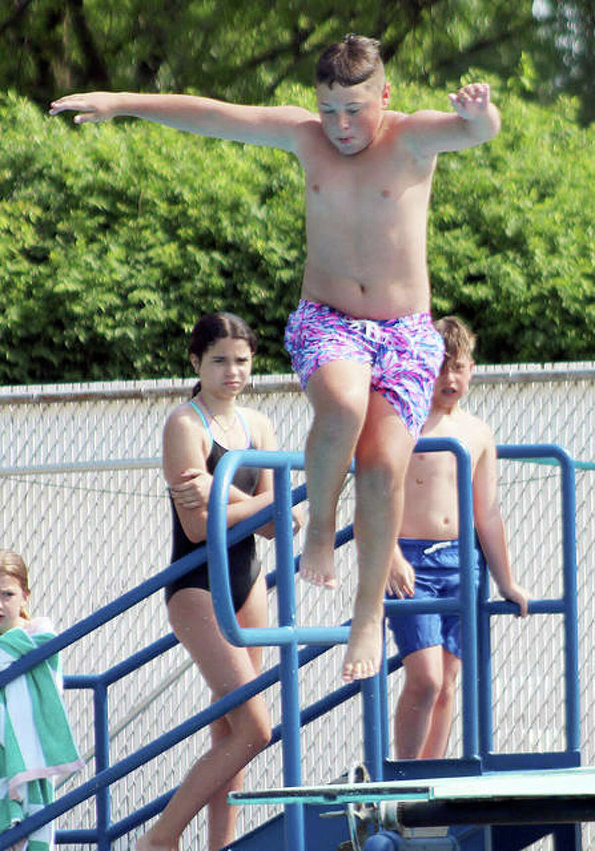 Luke Davis of Summers Port bounces on the end of the dive board as he dives during a practice at the Godfrey pool.