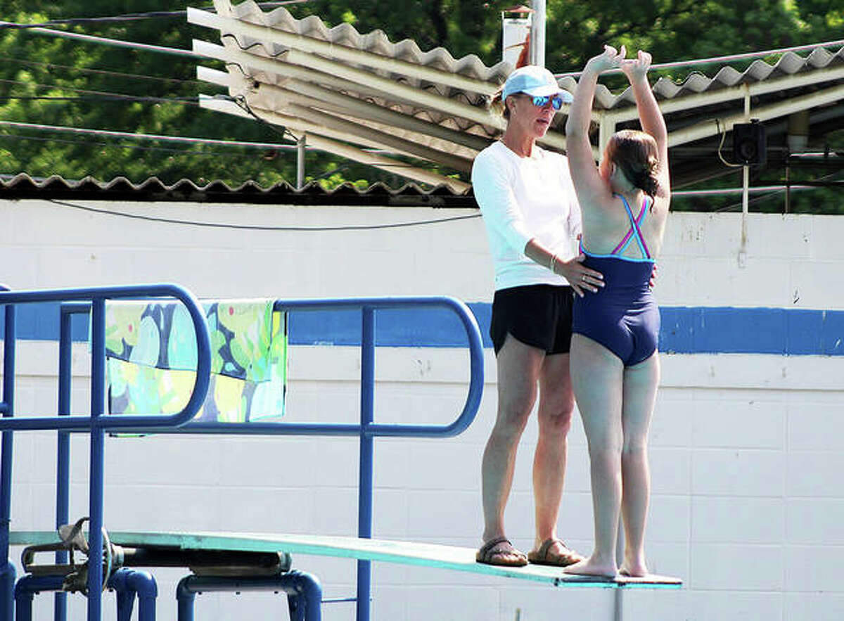 Summers Port Meme Evans helps diver Aubrey Rickman out on the dive board as Rickman practices a back dive during a recent practice.