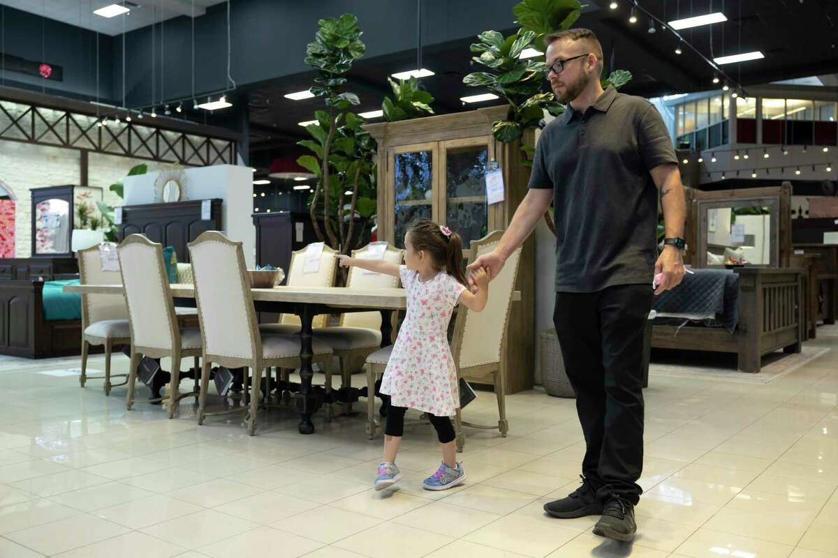 """U.S. Army Staff Sergeant Stephen Netzley holds his daughters hand, Mrazy Lago, as they look at furniture after being gifted a $20,000 gift certificate by Mattress Mack"""" Jim McIngvale at Gallery Furniture, Thursday, June 17, 2021, in Houston. Netzley was awarded a mortgage free home in Bridgeland by the Howard Hughes Corporation and Operation Finally Home."""
