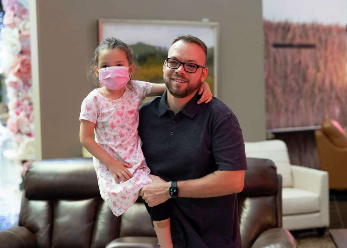 """U.S. Army Staff Sergeant Stephen Netzley holds onto his daughter, Mrazy Lago, as they look at furniture after being gifted a $20,000 gift certificate by Mattress Mack"""" Jim McIngvale at Gallery Furniture, Thursday, June 17, 2021, in Houston. Netzley was awarded a mortgage free home in Bridgeland by the Howard Hughes Corporation and Operation Finally Home."""
