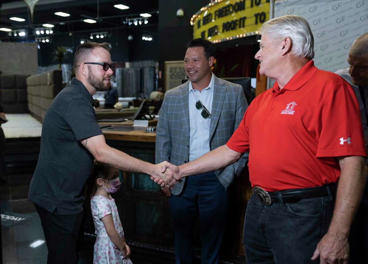 """U.S. Army Staff Sergeant Stephen Netzley, left, shakes hands with Lee Kirgan, vice president of project management of Operation Finally Home, after being gifted a $20,000 gift certificate by Mattress Mack"""" Jim McIngvale at Gallery Furniture, Thursday, June 17, 2021, in Houston. Netzley was awarded a mortgage free home in Bridgeland by the Howard Hughes Corporation and Operation Finally Home."""