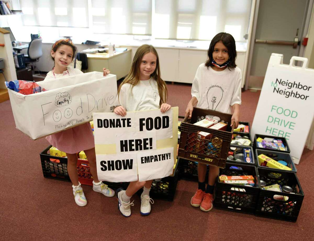 Fifth-graders Olivia Tenente, left, Macky Wilson, center, and Yasmine Bruce pose alongside the food they collected for Neighbor to Neighbor at the International School at Dundee in the Riverside section of Greenwich, Conn. Thursday, June 17, 2021. To go along with a school project called Empathy in Action, the three ISD fifth-graders led a food drive in which they collected more than 100 pounds of nonperishable food to be donated to the local food pantry Neighbor to Neighbor.