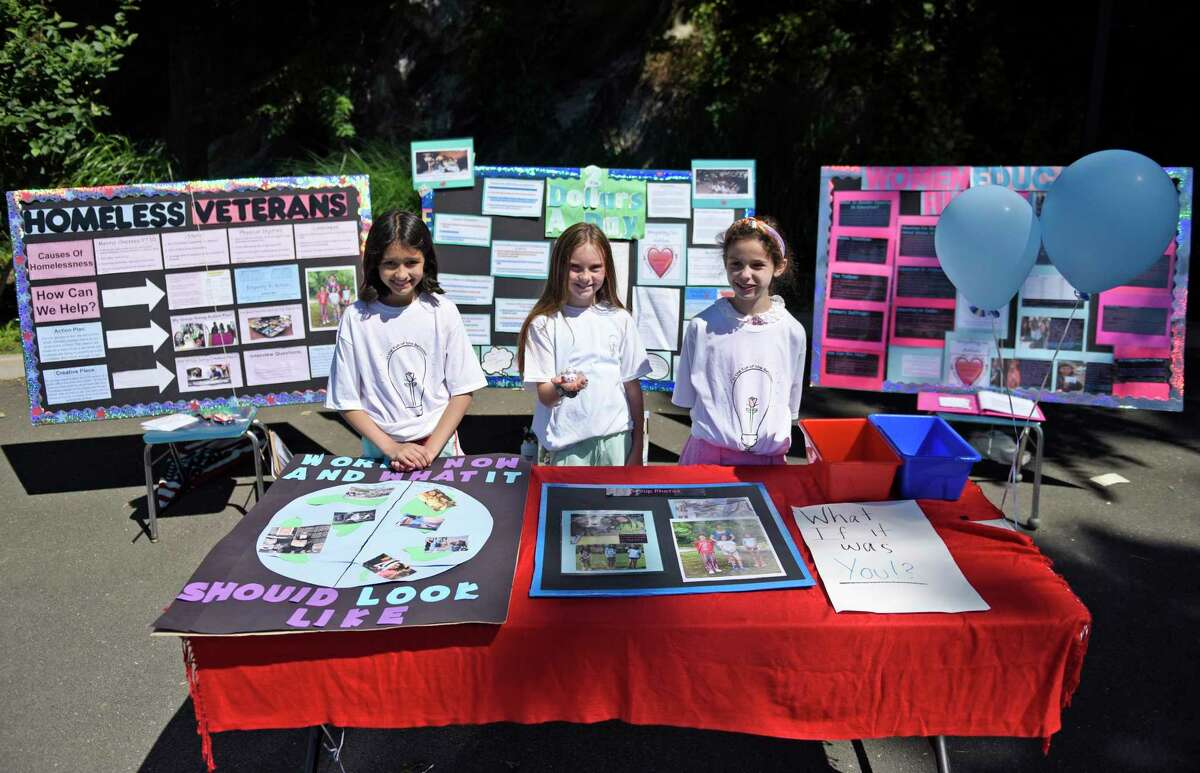 Fifth-graders Yasmine Bruce, left, Macky Wilson, center, and Olivia Tenente pose pose by their Empathy in Action projects at the International School at Dundee in the Riverside section of Greenwich, Conn. Thursday, June 17, 2021. To go along with the Empathy in Action project, the three ISD fifth-graders led a food drive in which they collected more than 100 pounds of nonperishable food to be donated to the local food pantry Neighbor to Neighbor.