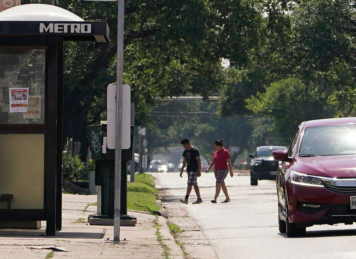 People are shown along Gulfton near a bus stop on June 17, 2021 in Houston. A new circulator is intended to increase frequency of transit in the neighborhood.