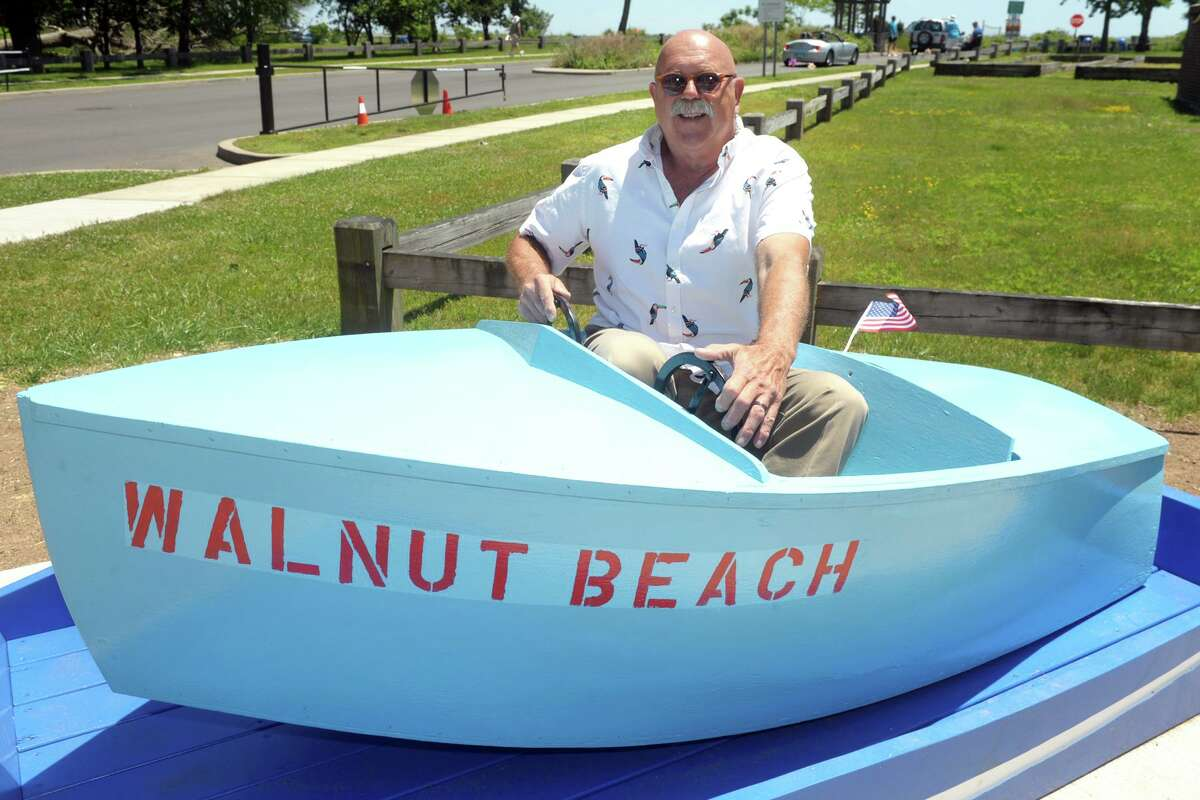 Max Nowicki sits in one of the old boats he and his family have saved from a ride at the former Walnut Beach Amusement Park, in Milford, Conn. June 17, 2021. Nowicki recently refurbished a couple of the boats, which are now on display at Walnut Beach.
