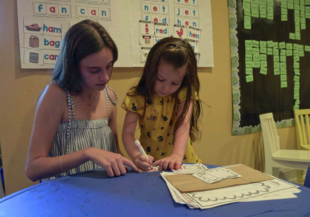 Teacher Jordan Roth works with Piper Howatt. Several families in Ridgefield decided to form a pod this past year for their kindergartners instead of sending them to school. They hired Roth and held class in one of their homes. Wednesday, June 16, 2021, in Ridgefield, Conn.