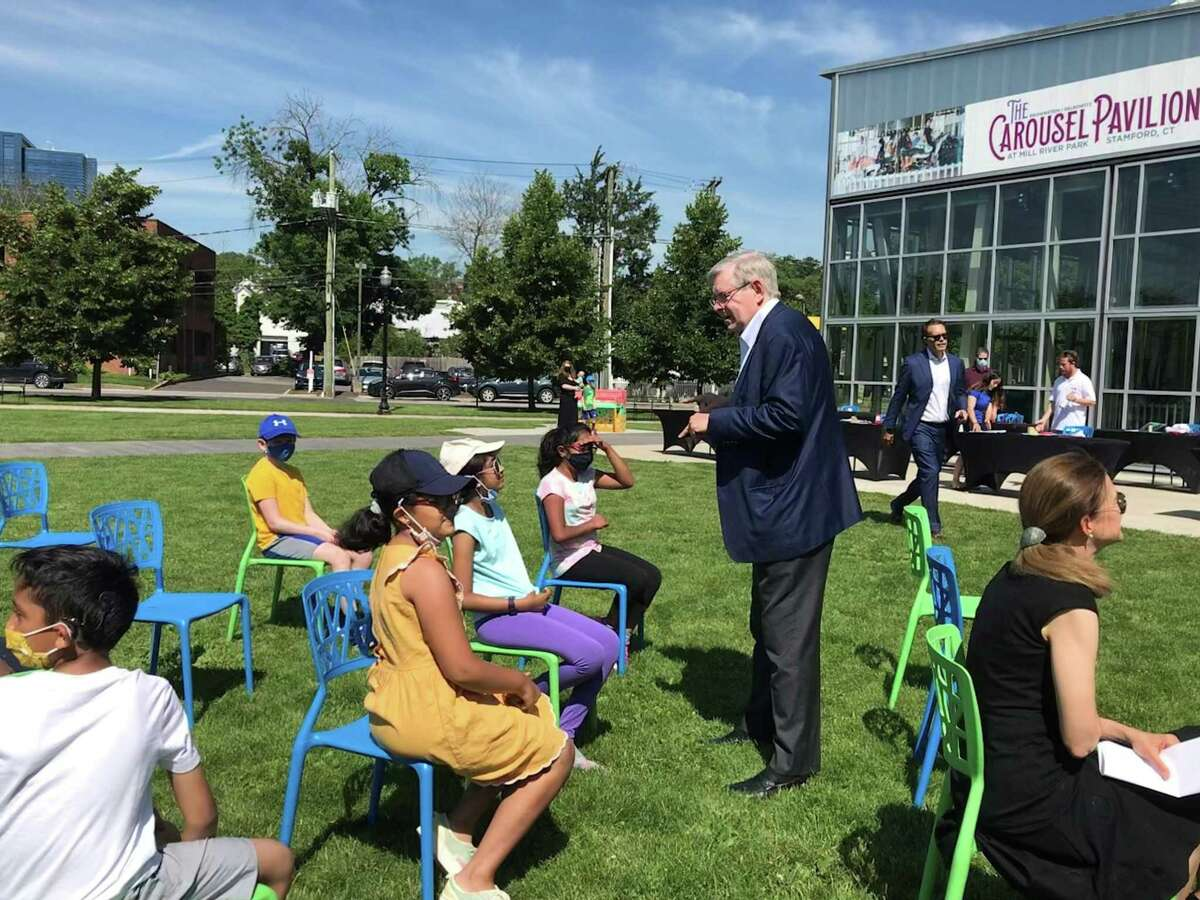 """Mayor David Martin speaks with children participating in a """"Researchers' World"""" workshop at Mill River Park in Stamford. The international company Henkel founded """"Researchers' World,"""" a program for children to learn about science. Stamford is the first U.S. city to host the program."""