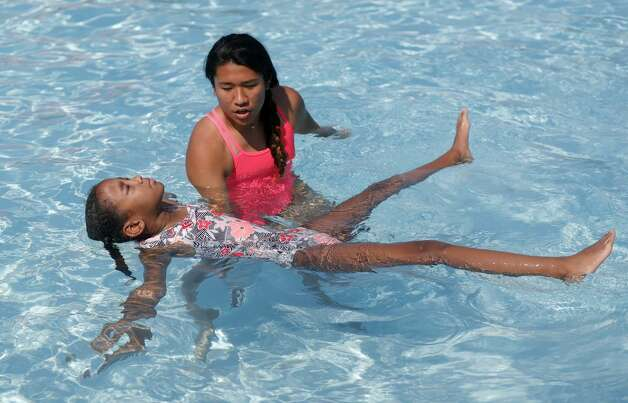 Instructor Elisa Gomez, top, helps Leeyah Lewis work on floating as more than 100 youth from around Montgomery County took part in this year's World's Largest Swimming Lesson at the City of Conroe Water Park, Friday, June 18, 2021, in Conroe. The WLSL event occurs once a year where participating groups take part in the same swim lesson across 48 countries. Since beginning in 2010, the event has reached 320,000 people and serves as a platform to help the global aquatics industry work together to build awareness about the fundamental importance of teaching children to swim to prevent drowning. Photo: Jason Fochtman/Staff Photographer / 2021 © Houston Chronicle