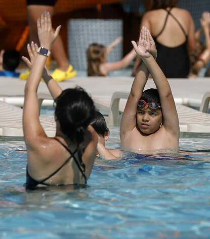 Jayden Dominguez, left, mirrors proper diving technique as more than 100 youth from around Montgomery County took part in this year's World's Largest Swimming Lesson at the City of Conroe Water Park, Friday, June 18, 2021, in Conroe. The WLSL event occurs once a year where participating groups take part in the same swim lesson across 48 countries. Since beginning in 2010, the event has reached 320,000 people and serves as a platform to help the global aquatics industry work together to build awareness about the fundamental importance of teaching children to swim to prevent drowning. Photo: Jason Fochtman/Staff Photographer / 2021 © Houston Chronicle
