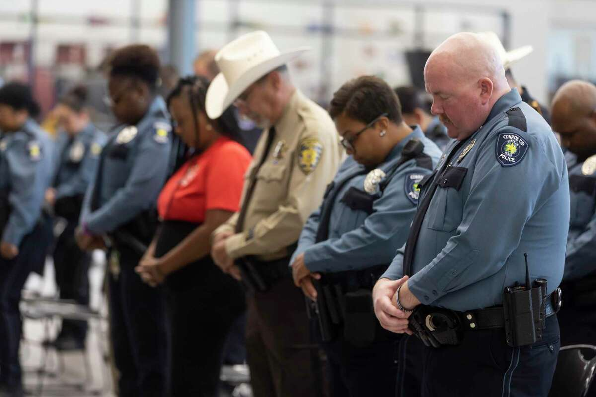 Officers with Conroe ISD Police partake in a prayer during a graduation ceremony from training with the D.A.R.E. program at Stockton Junior High School, Friday, June 18, 2021, in Conroe. The program lasted approximately two weeks.