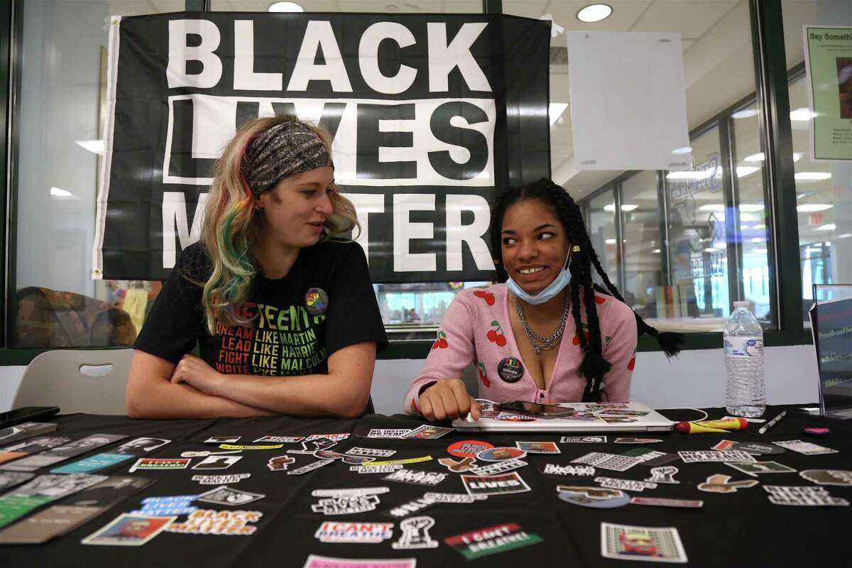 Teacher and advisor Kayla Iannetta, left, and student Emorej Hunter, 16, at a table offering stickers and other items to students in commemoration of Juneteenth.