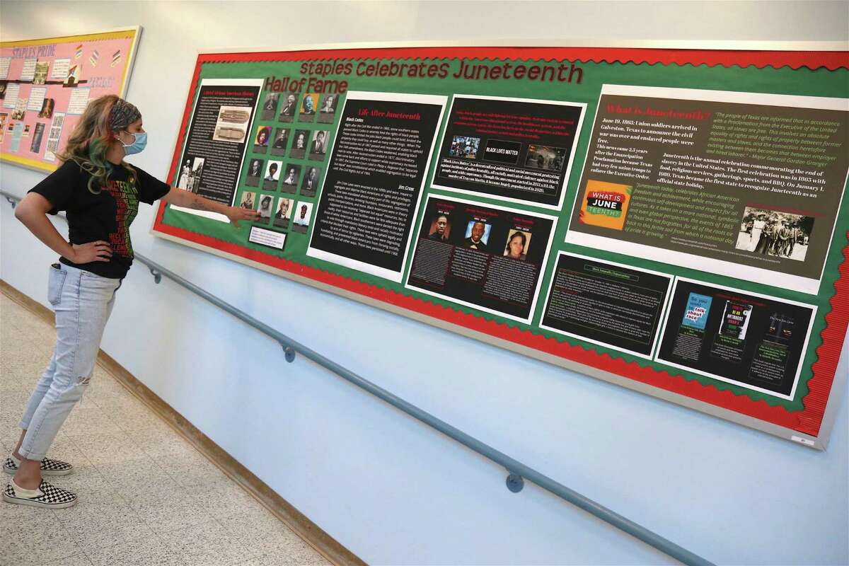 Teacher Kayla Iannetta shares the bulletin board with information on Juneteenth Day at Staples High School in Westport, Conn.