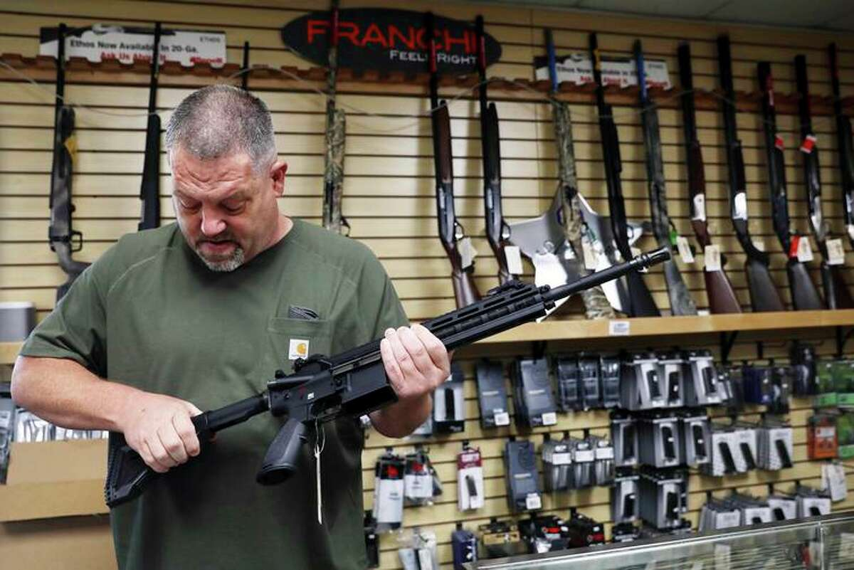 John Parkin, owner Coyote Point Armory, demonstrates the adjustable stock on an HK 416 and 22 long rifle, one of the featues of an AR-15 that required an owner to register it in California as an assault weapon, on Tuesday, June 15, 2021 in San Mateo, Calif. The HK 416 and 22 long rifle is not categorized as an assault weapon. A U.S. federal judge overturned the California's decades-old ban on the sale of assault weapons.