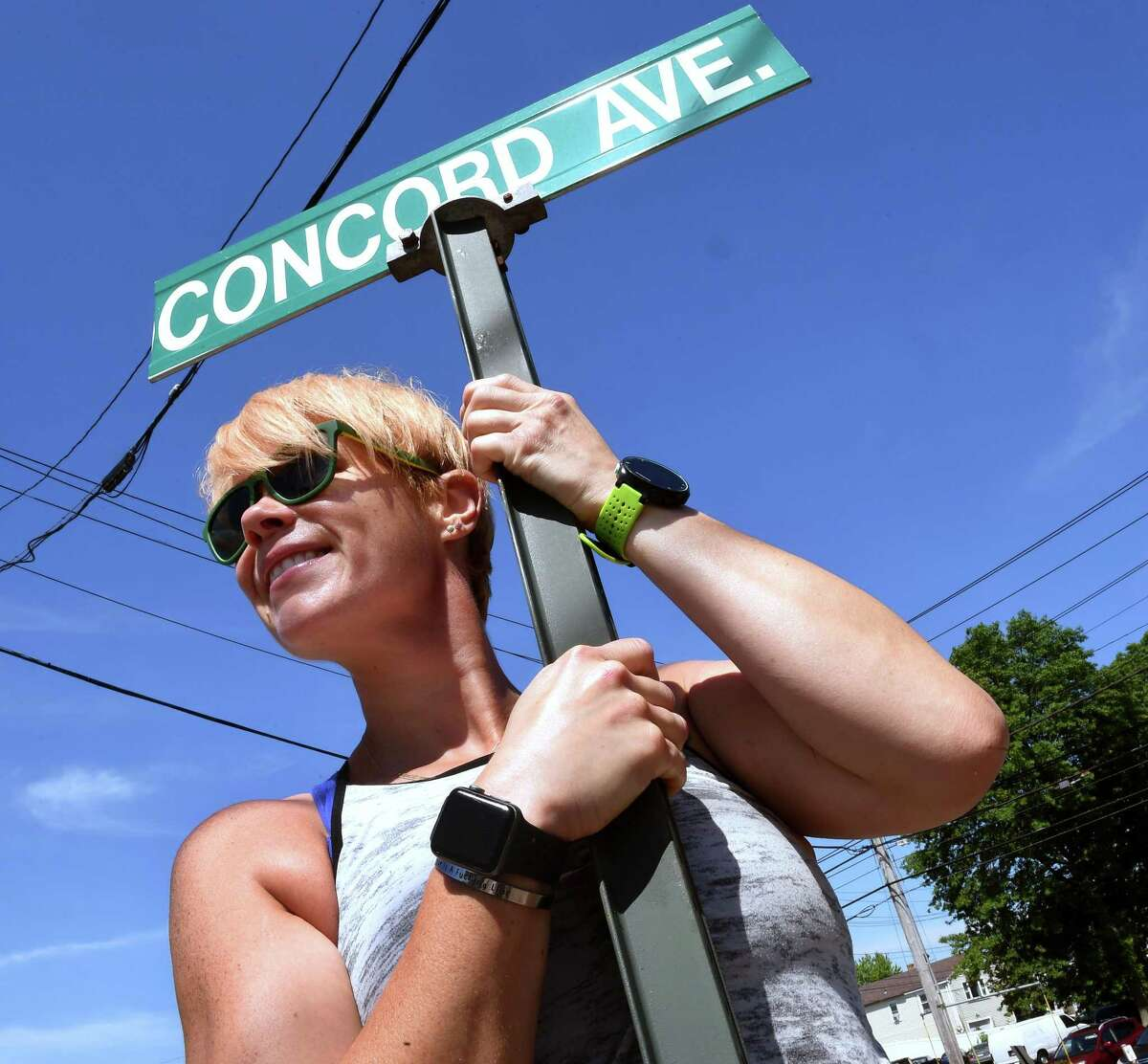 Tiffany McGuire holds onto the Concord Avenue street sign in Milford on June 18, 2021 where she began her quest to run on every street in the town.