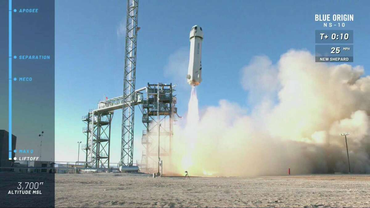 In this image from video made available by Blue Origin, the New Shepard capsule and booster lifts off from the company's site in west Texas in 2021, when Jeff Bezos' rocket company launched NASA experiments into space for a brief test flight. Now, Bezos says he and his brother will ride the along on the next flight.