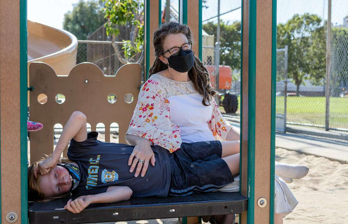 Jasper Barringhaus and his mother, Katie Pollard, visit Jackson Park playground in San Francisco. Pollard must weigh COVID risks against more than a year of social isolation and the mental health effects on her sons.