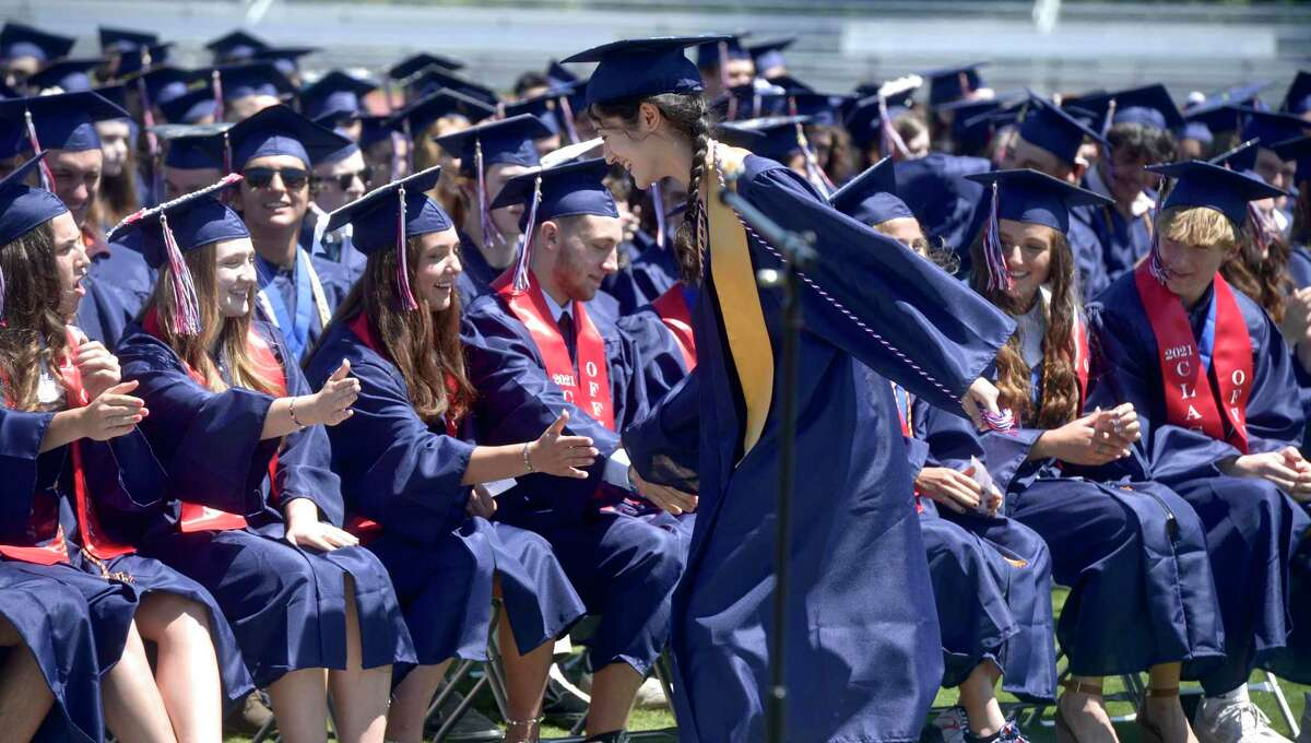 Class Valedictorian Anna Kozloski gets high fives on the way back to her chair after giving her address during the New Fairfield High School Class of 2021 Commencement Exercises. Friday morning, June 18, 2021, in New Fairfield, Conn.