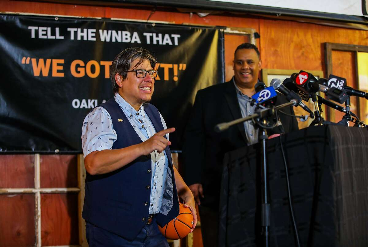 Oakland Vice Mayor Rebecca Kaplan holds a basketball while sharing the stage with Ray Bobbitt of AASEG.
