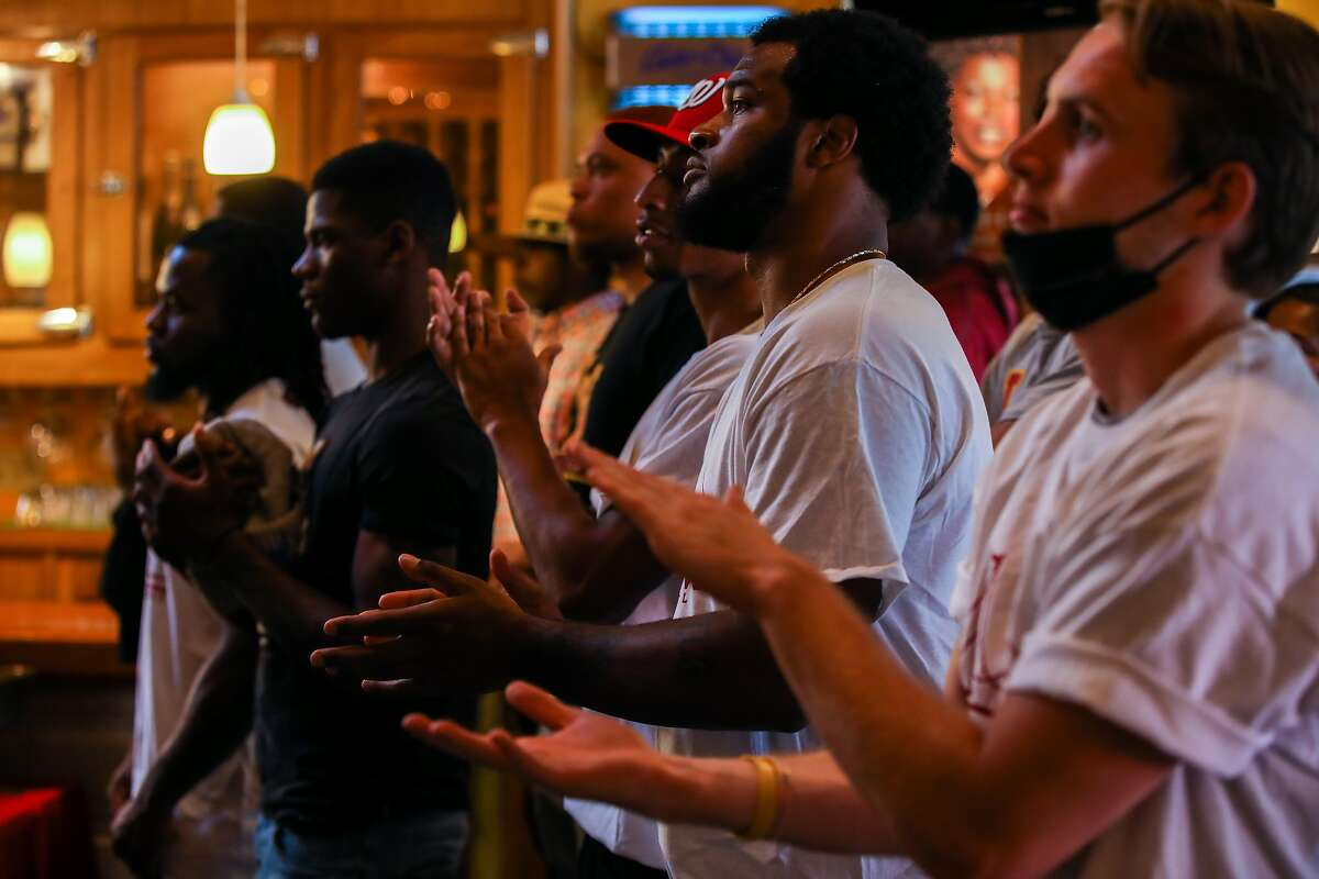 Audience members applaud during a press conference led by Ray Bobbitt, founder of African American Sports & Entertainment Group.