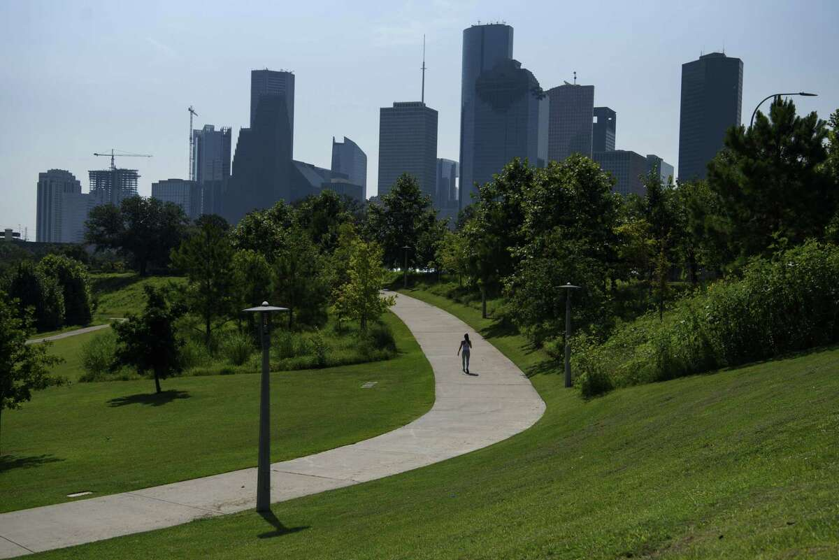 A person walks through Buffalo Bayou Park during a heatwave in Houston, Texas, U.S., on Thursday, June 17, 2021. Texas is pushing homes and businesses to conserve electricity for a second day in a row to stave off blackouts as a punishing heat wave bakes the western U.S. Photographer: Callaghan O'Hare/Bloomberg