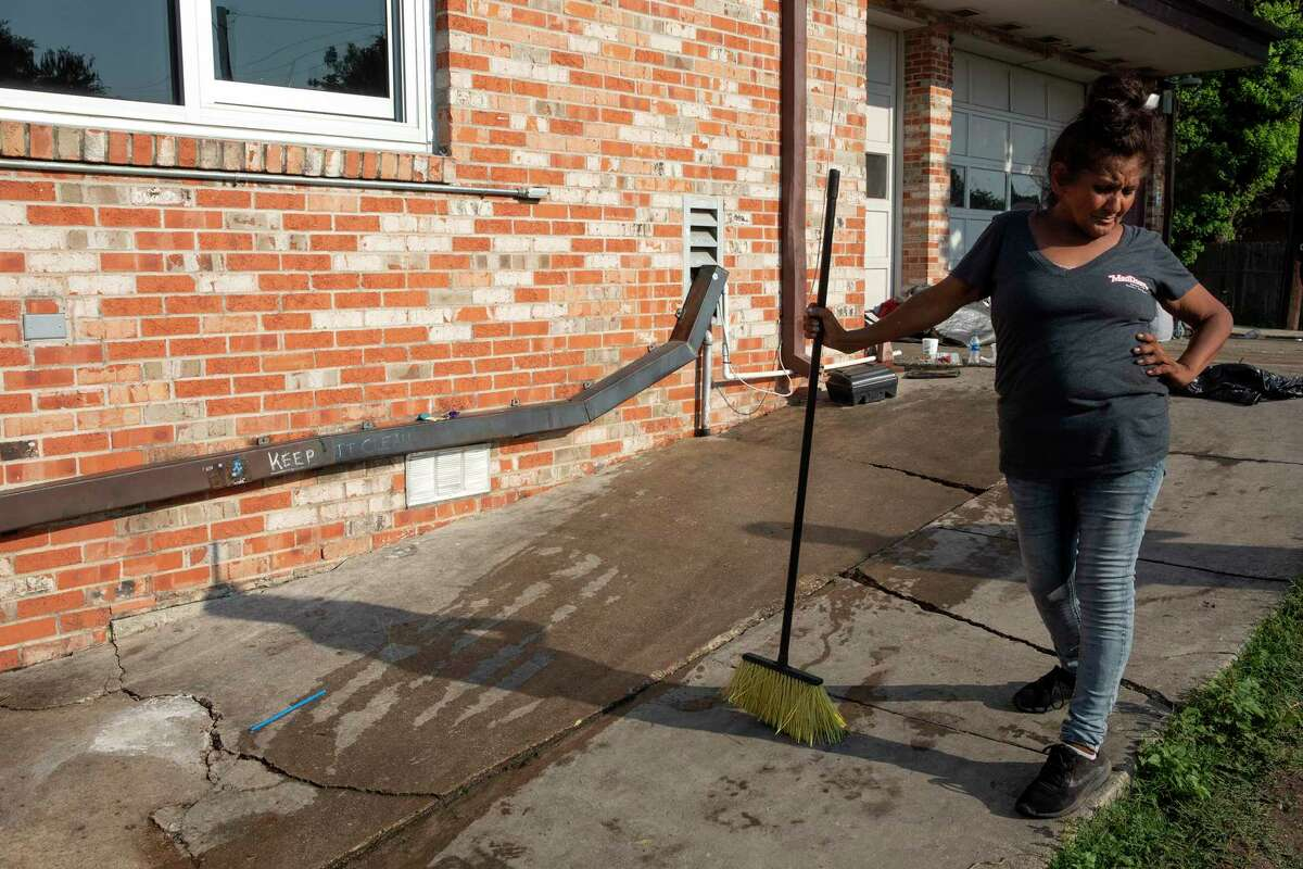 Rosa pauses from cleaning a section of a sidewalk next to the District 1 field office parking lot where people of have been camping. Rosa, who does not sleep at the parking lot anymore, wants to help keep it clean for friends that are still there.