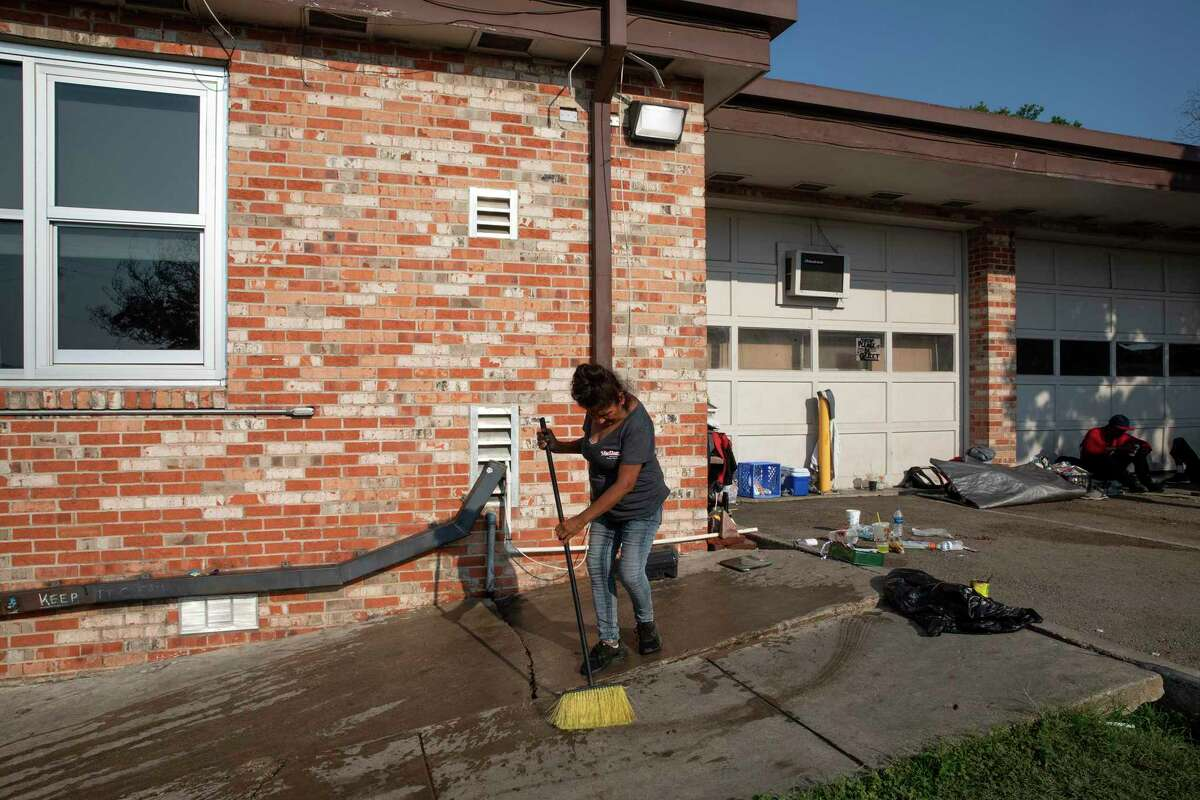 Rosa cleans a section of a sidewalk next to the District 1 field office parking lot where unsheltered people of have been camping. Rosa, who does not sleep at the parking lot anymore, wants to help keep it clean for her friends that are still there.