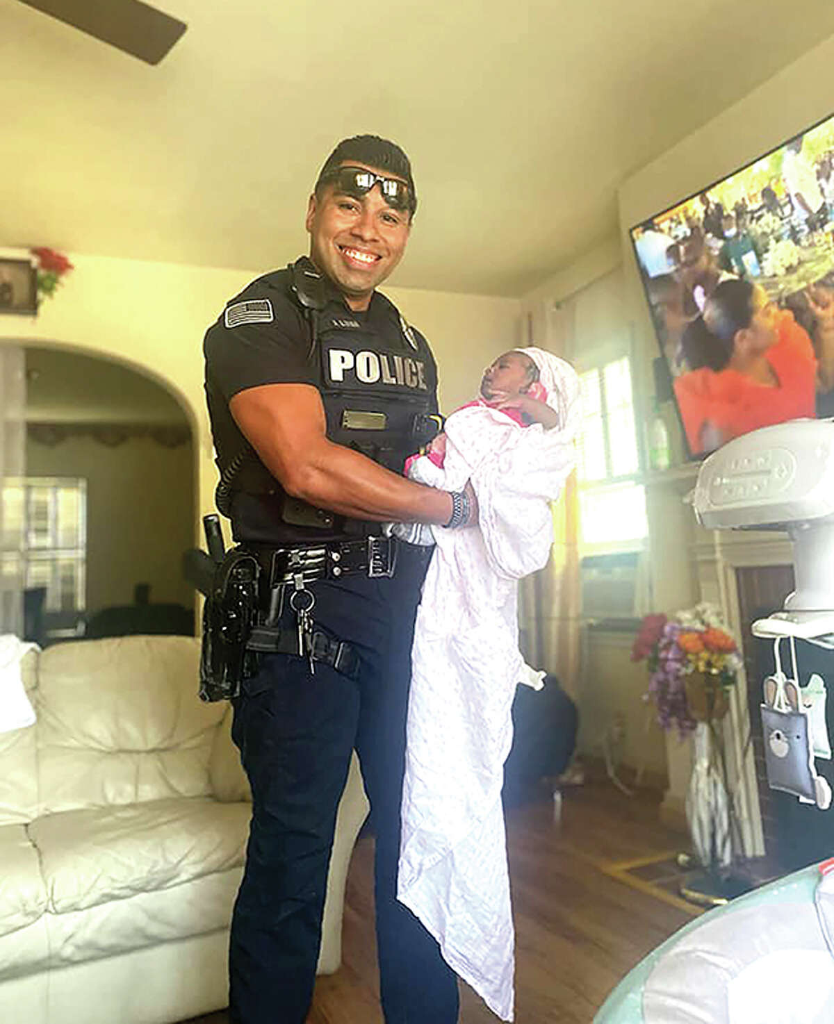 Joey Luna, a Beardstown police officer, holds a new baby he helped deliver earlier this month.