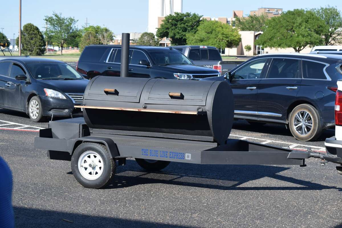 """A while back, the late Robert Rivera asked his friend, H.T. Sanchez to build him a grill. Sanchez, superintendent of Plainview ISD, likes to weld. It's a hobby he enjoys when taking a break from running the district. Rivera, an officer for Plainview ISD, approached Sanchez with a design and Sanchez happily agreed. He started the project but didn't finish it before Rivera's untimely death from COVID-19 in December. Sanchez continued the project consulting with friends who are welders and with local artist Rigo Rey (who helped create a logo design for the grill) and finished the project in memory of their friend. On Thursday, Sanchez presented the grill - which has blue letters in the corner that say """"The Blue Line Express"""" - to Rivera's wife, Sofia. Sofia shed some surprised tears and thanked Sanchez joking that she and her daughters would have to learn how to grill."""