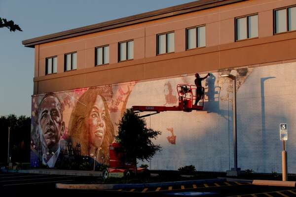 Ryan Christenson, of North Haven, who goes by ARCY, paints the wall of Alvin and Beatrice Wood Human Services Center, a community center in Bloomfield. Barack Obama, left, and Anika Rose, a Bloomfield native, are painted on the wall.