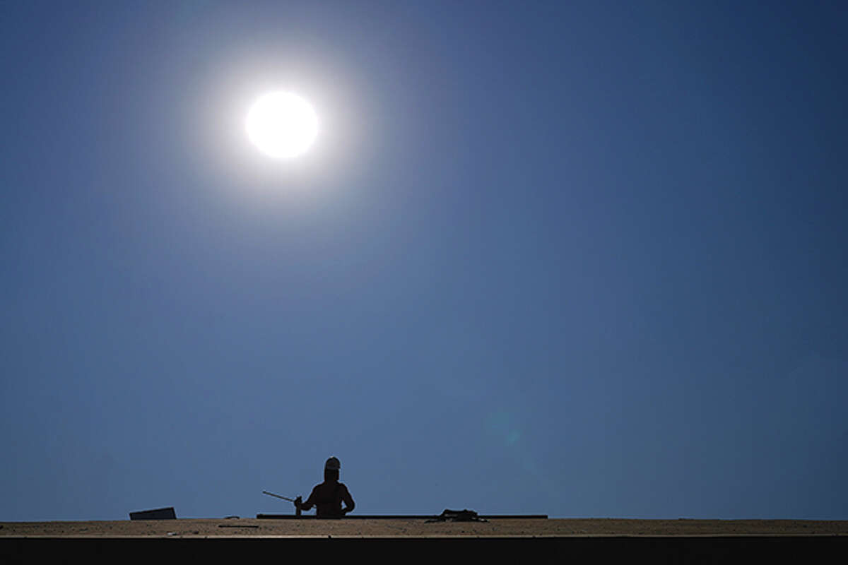 A roofer works at a housing development as the sun beats down on him.