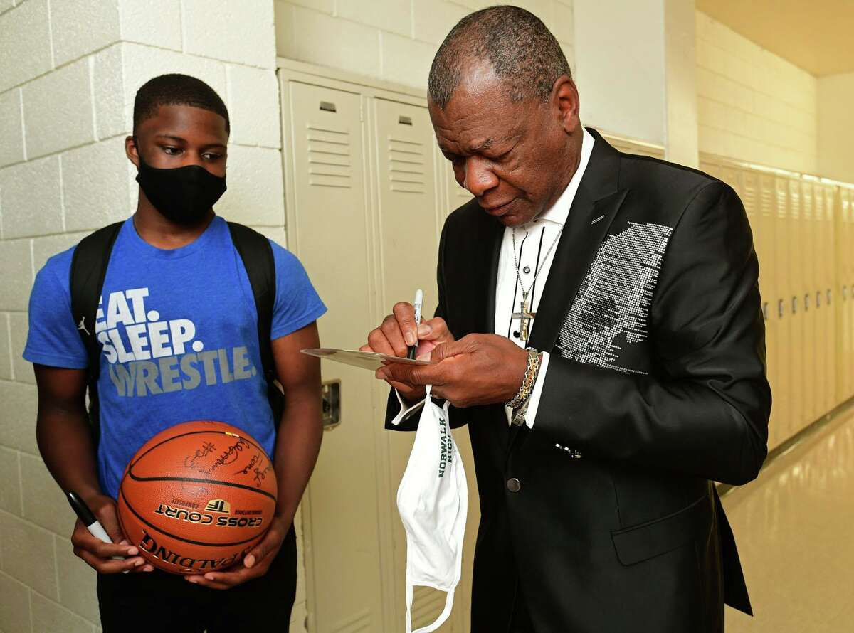 Basketball Hall of Famer and Norwalk High School alumni Calvin Murphy signs memorabilia for alumni, fans and students, including high school junior Sean Paul Joseph as Murphy returns to the school for first time in several years for program Friday, June 18, 2021, in Norwalk, Conn.