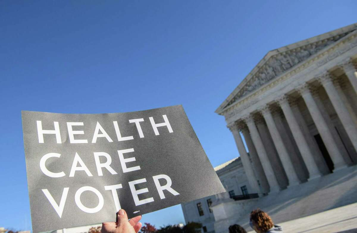 In this file photo taken on November 10, 2020, a demonstrator holds a sign in front of the U.S. Supreme Court in Washington, DC, as the court opened arguments in a case over the constitutionality of the 2010 Affordable Care Act. The Court on June 17, 2021, rejected a Texas-led challenge to former President Barack Obama's health care program in a 7-2 decision.