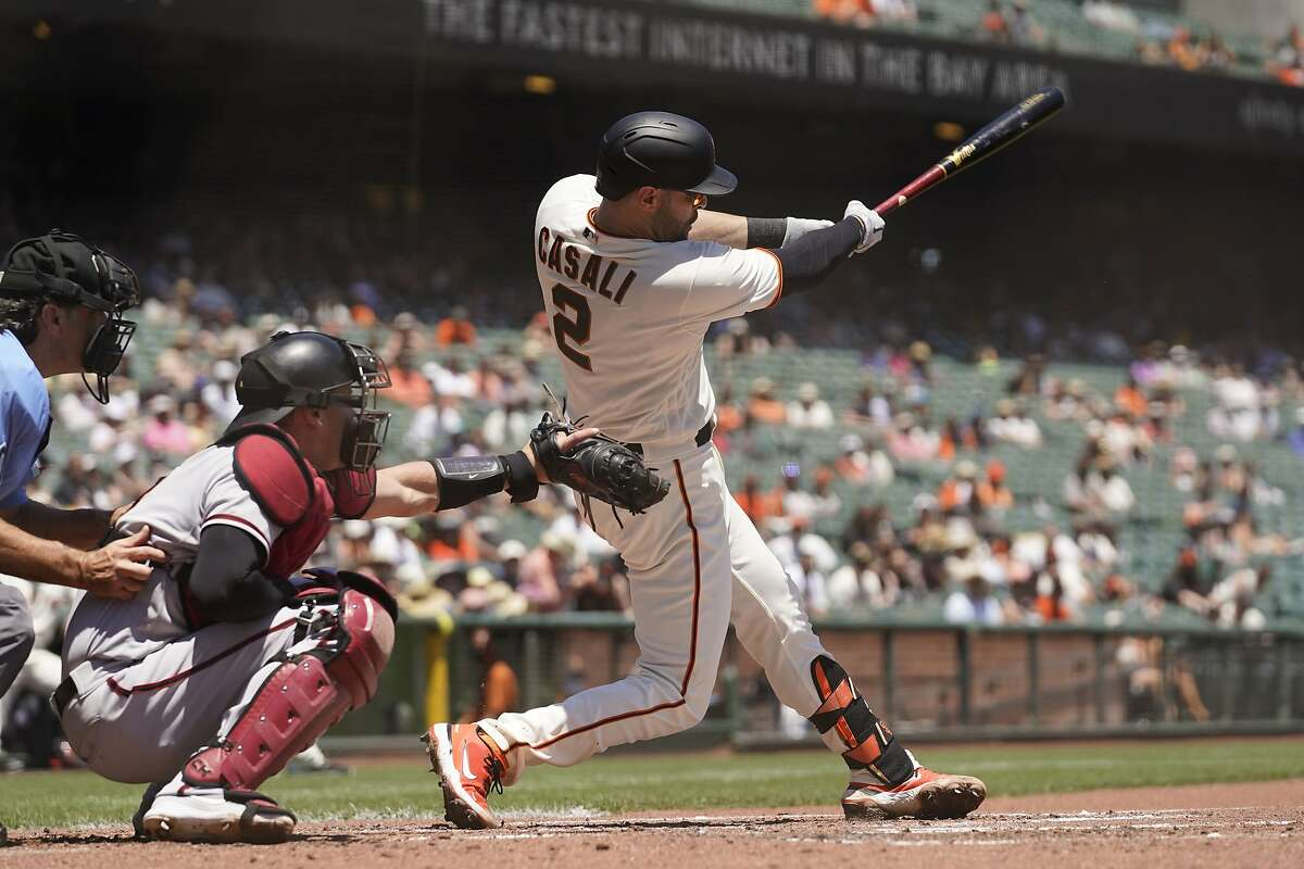 San Francisco Giants' Curt Casali, right, hits a two-run home run off Arizona Diamondbacks starting pitcher Zac Gallen in the second inning of a baseball game Thursday, June 17, 2021, in San Francisco. Diamondbacks catcher Carson Kelly, center, and home plate umpire Phil Cuzzi, left, look on. (AP Photo/Eric Risberg)