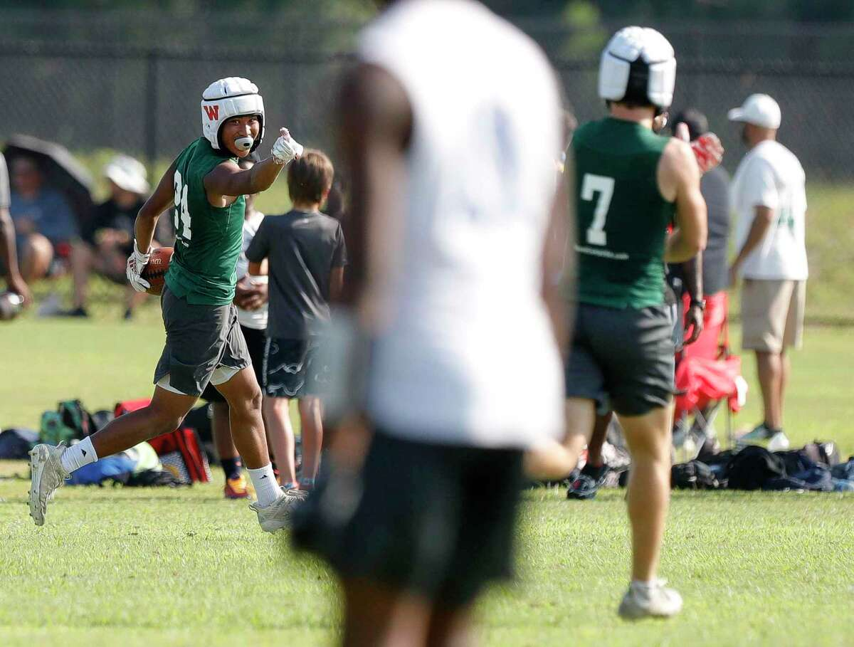 The Woodlands defensive back Kaiden Villaver celebrates after returning an interception for a touchdown during a 7-on-7 football tournament at Grand Oaks High School, Friday, June 18, 2021, in Spring.