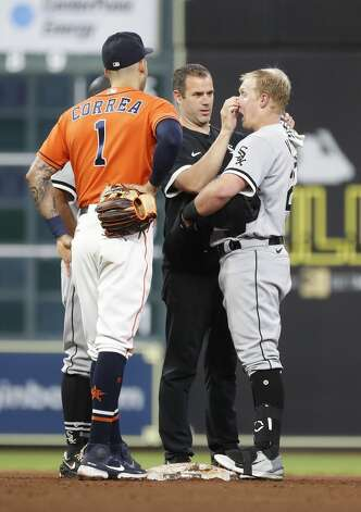 Chicago White Sox head athletic trainer James Kruk checks on Andrew Vaughn (25) after he was hit in the face by a throw from Houston Astros right fielder Chas McCormick on Vaughn's double as Carlos Correa looks on during the sixth inning of an MLB baseball game at Minute Maid Park, Friday, June 18, 2021. Photo: Karen Warren/Staff Photographer / @2021 Houston Chronicle