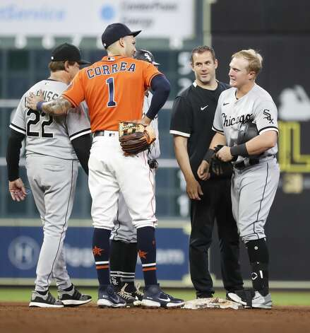Chicago White Sox head athletic trainer James Kruk checks on Andrew Vaughn (25) after he was hit in the face by a throw from Houston Astros right fielder Chas McCormick on Vaughn's double as Carlos Correa and manager Tony La Russa look on during the sixth inning of an MLB baseball game at Minute Maid Park, Friday, June 18, 2021. Photo: Karen Warren/Staff Photographer / @2021 Houston Chronicle