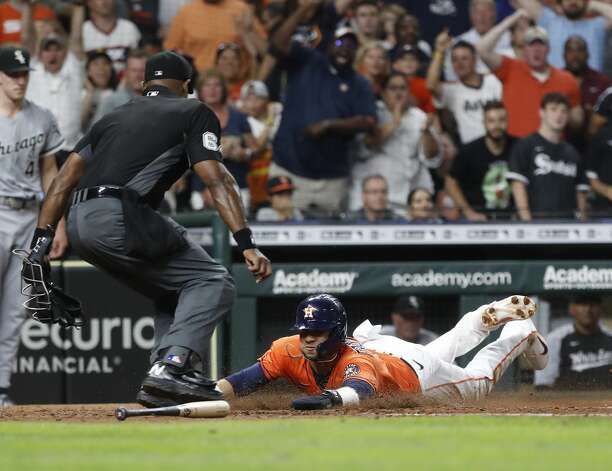 Houston Astros Yuli Gurriel (10) dives home to score the winning run on Yordan Alvarez's RBI double to beat the Chicago White Sox 2-1 during the ninth inning of an MLB baseball game at Minute Maid Park, Friday, June 18, 2021. Photo: Karen Warren/Staff Photographer / @2021 Houston Chronicle