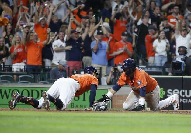 Houston Astros Carlos Correa (1) joins Yuli Gurriel (10) at home after he scored the winning run on Yordan Alvarez's RBI double to beat the Chicago White Sox 2-1 during the ninth inning of an MLB baseball game at Minute Maid Park, Friday, June 18, 2021. Photo: Karen Warren/Staff Photographer / @2021 Houston Chronicle